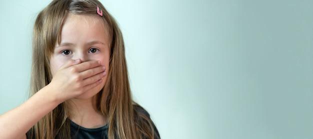 Портрет крупным планом маленькой девочки с длинными волосами, закрывающей рот рукой