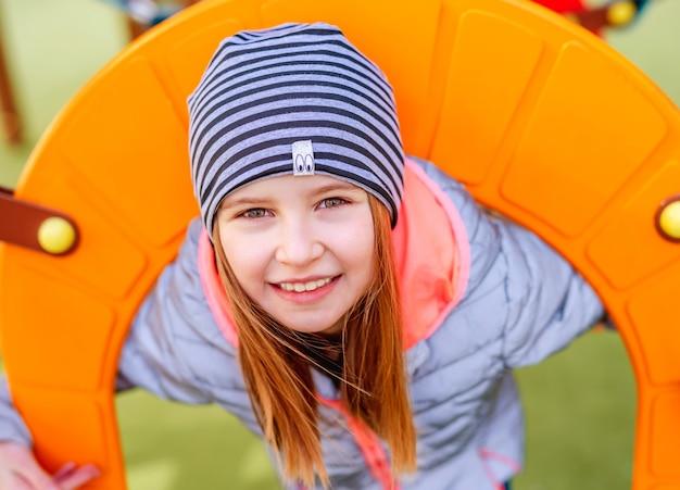 Портрет крупным планом маленькой улыбающейся девочки на детской площадке в осеннее время