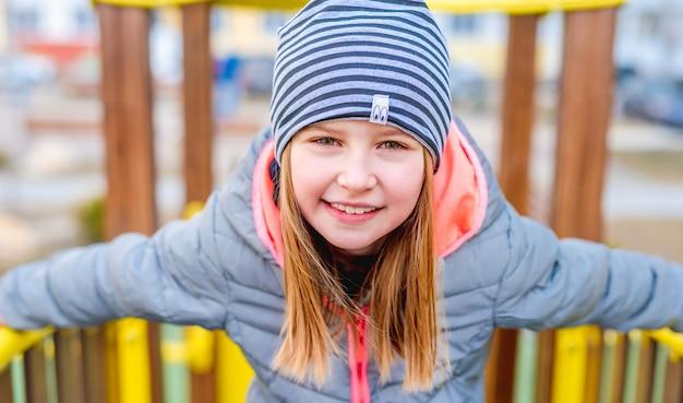 Портрет крупным планом маленькой улыбающейся девочки с красивыми зелеными серыми глазами на детской площадке в осеннее время