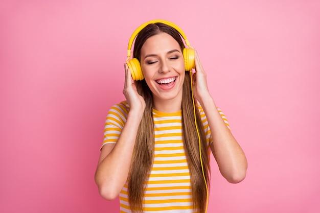 音楽のイヤホンを聴いて素敵な夢のような陽気な女の子のポートレート、クローズ アップ