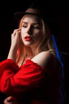 青と赤の光で影の中でポーズをとって、帽子をかぶって豪華なブロンドの女性のクローズアップの肖像画