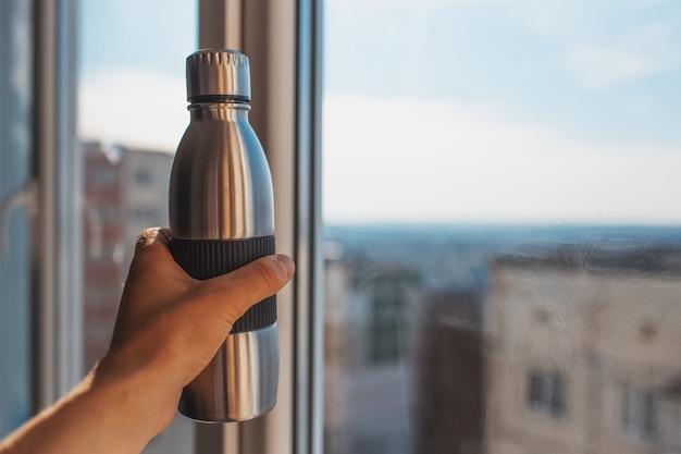 窓からの美しい景色の背景に、エコ鋼と再利用可能なサーモ ウォーター ボトルを持っている男性の手のクローズ アップの肖像画。