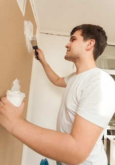 Портрет крупным планом человека, работающего шпателем и шпатлевкой на гипсокартонной стене