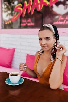 陽気な金髪の女性モデルのクローズアップの肖像画は、外でコーヒーを飲むジュエリーとヘッドアクセサリーを身に着けています