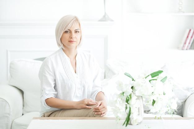 Крупным планом портрет midadult блондинка в помещении
