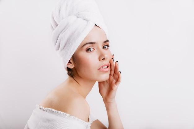 머리에 수건에 모델의 근접 촬영 초상화. 화장하지 않은 소녀가 부드럽게 얼굴을 만집니다.