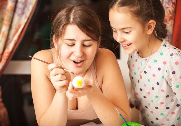 Портрет крупным планом матери и девочки, рисующей пасхальные яйца