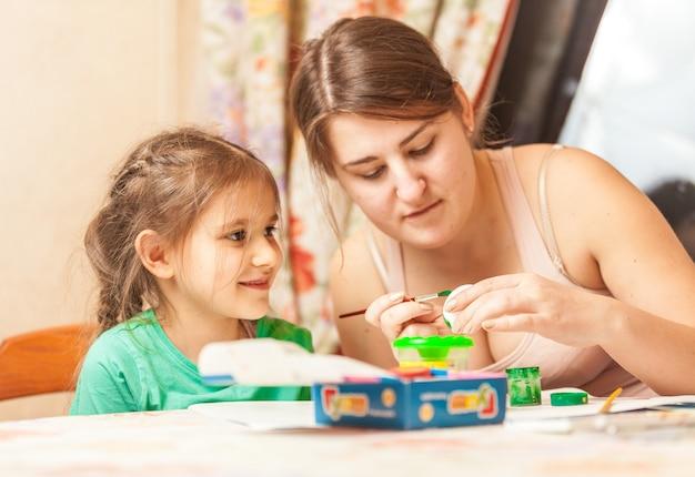 Портрет крупным планом матери, помогающей дочери рисовать пасхальное яйцо