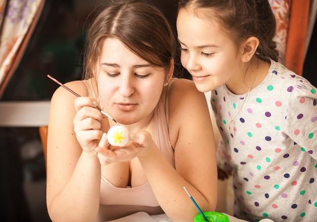 Портрет крупным планом матери показывает дочери, как красить яйца