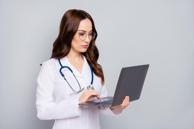 Портрет крупным планом симпатичного привлекательного квалифицированного волнистого врача-специалиста по фонендоскопу, стетоскопа, держащего в руках удаленную поддержку ноутбука, изолированного на сером пастельном цветном фоне