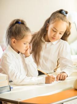 妹の宿題を手伝う姉のクローズ アップの肖像画