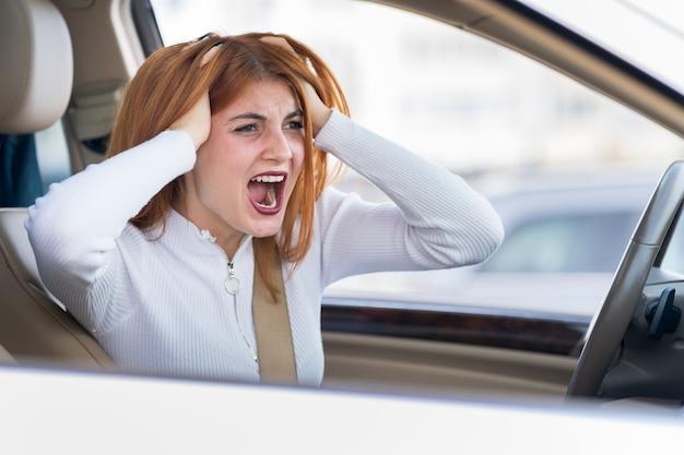 Крупным планом портрет разозлился недоволен злой агрессивной женщины за рулем автомобиля, крича на кого-то. отрицательное человеческое выражение conckerept.