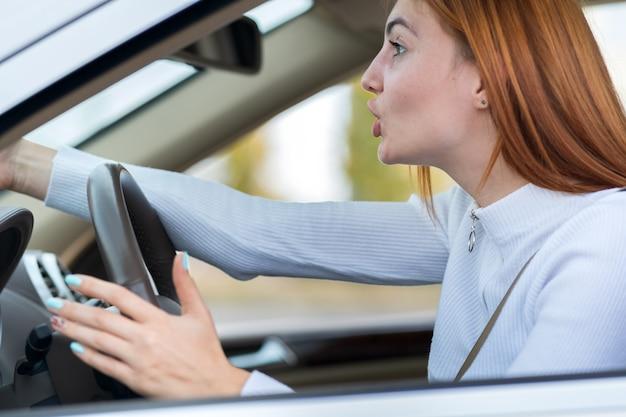 手拳で誰かに叫んで車を運転して不機嫌な怒っている積極的な女性の腹を立ててのクローズアップの肖像画。否定的な人間の表現の概念。