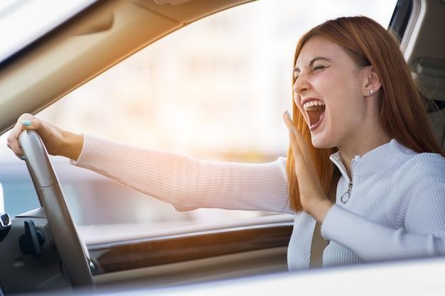 手拳で誰かに叫んで車を運転している不機嫌な怒っている攻撃的な女性の怒りのクローズアップの肖像画。否定的な人間の表現の概念。