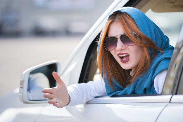手拳で誰かに叫んで車を運転して腹を立てて怒っている攻撃的な女性のポートレート、クローズアップ。負の人間の表現の概念。