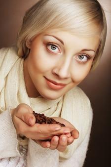 Портрет крупным планом довольно блондинка держит в руках горячие жареные кофейные зерна