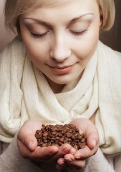 Крупным планом портрет довольно блондинка держит в руках горячие жареные кофейные зерна