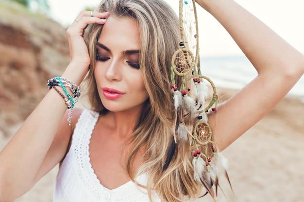 해변에 긴 머리를 가진 금발 여자의 근접 촬영 초상화. 그녀는 깃털로 장식을 손에 들고 눈을 감고 있습니다.