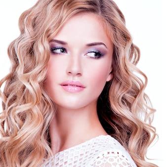 波状の髪の側を見てかわいいブロンドの女の子のクローズアップの肖像画-白で隔離。
