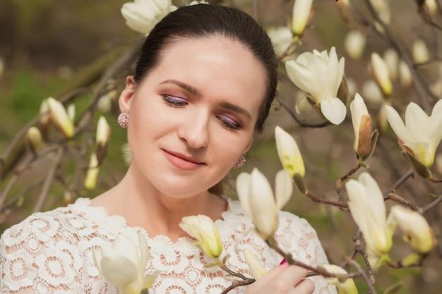咲くモクレンの花の近くでポーズをとってヌードメイクでかなりブルネットの女性のクローズアップの肖像画