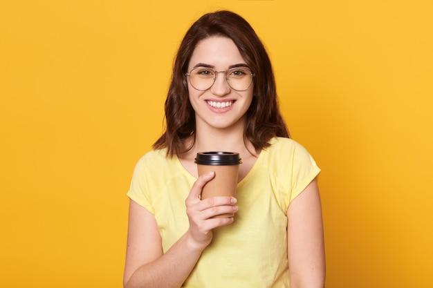 カジュアルなtシャツとメガネでかなり陽気なブルネットの少女のポートレート、クローズアップ、コーヒーを奪う