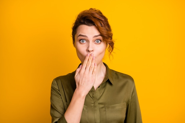 Портрет крупным планом красивой девушки, закрывающей рот, храня в секрете