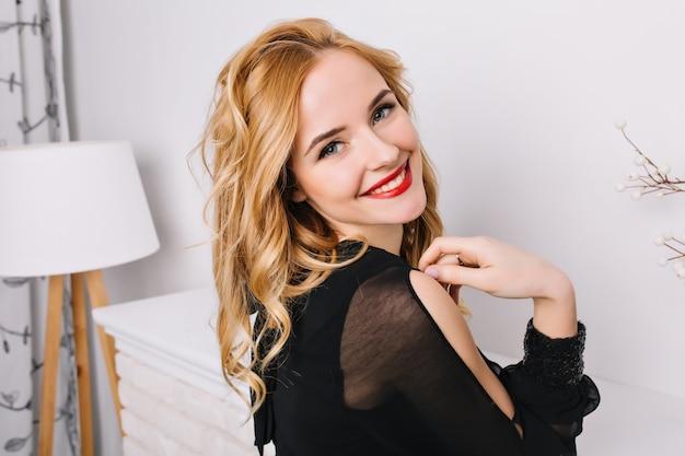 Крупным планом портрет красивой девушки со светлыми волнистыми волосами, улыбаясь, позирует в белой современной комнате. вид сбоку. одет в стильное черное платье, блузку.