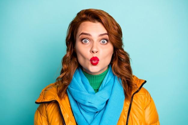 공기를 보내는 예쁜 아가씨의 근접 촬영 초상화 잘 생긴 남자 수줍은 사람이 캐주얼 노란색 외투 파란색 스카프 녹색 터틀넥을 착용 키스.
