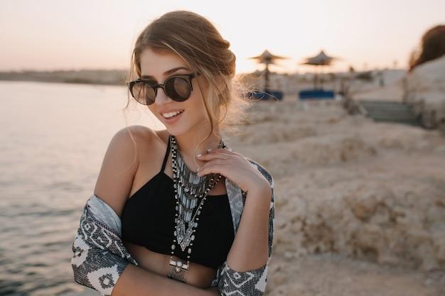官能的な表情でビーチで、日没でかなり若い女性のポートレート、クローズアップ。トレンディなブラックトップ、スタイリッシュなサングラス、ネックレス、カーディガン、飾り付きのケープを着ています。