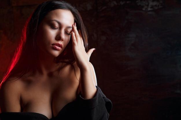 スタジオで赤い光でポーズをとって、裸の肩を持つ悲しいモデルのクローズアップの肖像画。テキスト用のスペース