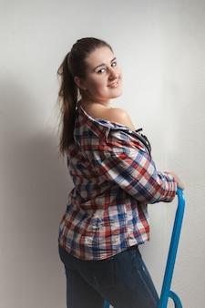 Портрет крупным планом соблазнительной женщины в рубашке, сидящей на металлической лестнице