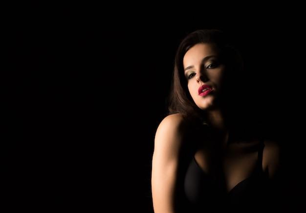 어둠 속에서 벌거 벗은 어깨와 함께 포즈를 취하는 밝은 저녁 화장을 한 매혹적인 여성의 근접 촬영 초상화