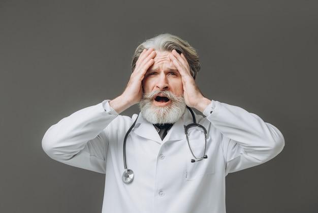 Макрофотография портрет старшего специалиста здравоохранения, подчеркнул, перегружены врач, со стетоскопом, изолированные на серую стену