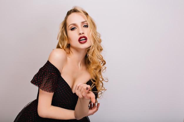 官能的な唇でセクシーなブロンドの女の子、巻き毛のヘアスタイル、手招きの指でポーズをとって情熱的な若い女性のポートレート、クローズアップ。素敵な黒いドレスを着て、メイク。