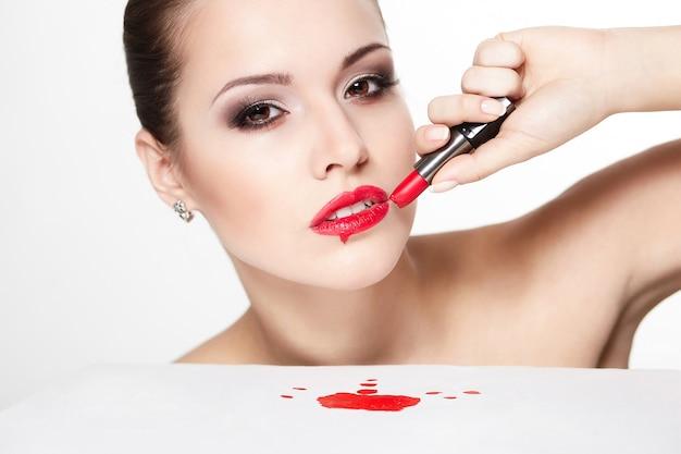 グラマー赤い唇、明るいメイク、アイ矢印メイク、赤い口紅と純度の顔色を持つセクシーな白人若い女性モデルのクローズアップの肖像画。完璧なきれいな肌。テーブルの上の血