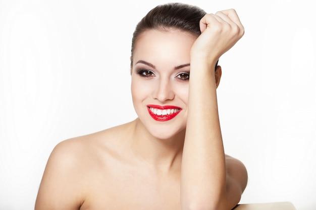 グラマー赤い唇、明るいメイク、アイ矢印メイク、純度の顔色とセクシーな笑みを浮かべて白人若い女性モデルのクローズアップの肖像画。完璧なきれいな肌。白い歯