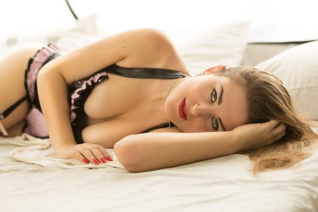Крупным планом портрет сексуальная женщина в нижнем белье, лежа на кровати и глядя в камеру