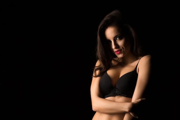 影の中で裸の肩でポーズをとって明るい夜のメイクでセクシーな女性のクローズアップの肖像画