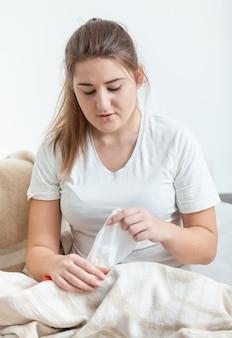상자에서 종이 티슈를 당기는 아픈 여자의 근접 촬영 초상화