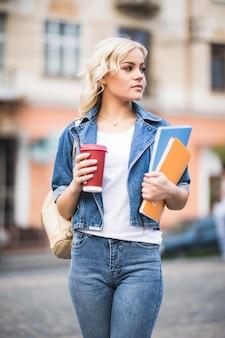 Портрет крупным планом улыбающейся блондинки-студентки с большим количеством ноутбуков, одетой в джинсы