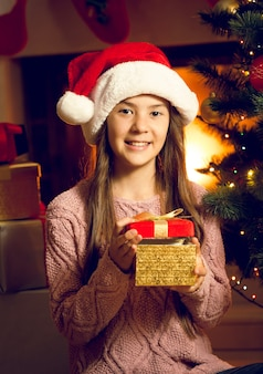 赤いギフトボックスを保持しているサンタの帽子の笑顔の女の子のクローズアップの肖像画
