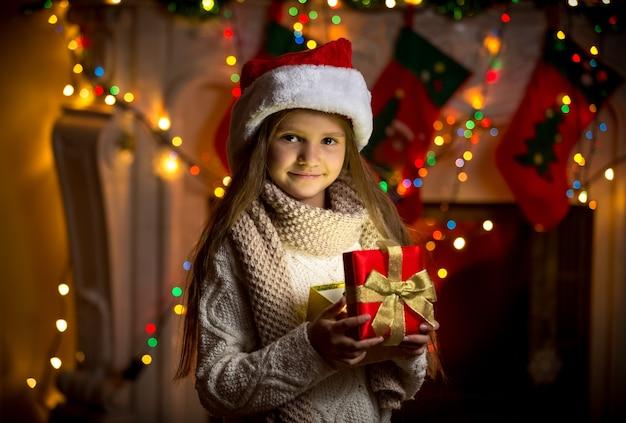 크리스마스에 반짝이 선물 상자를 여는 웃는 소녀의 근접 촬영 초상화