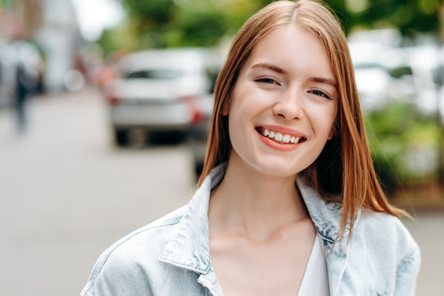 Портрет крупного плана усмехаясь женщины красно-волос стоя напольной