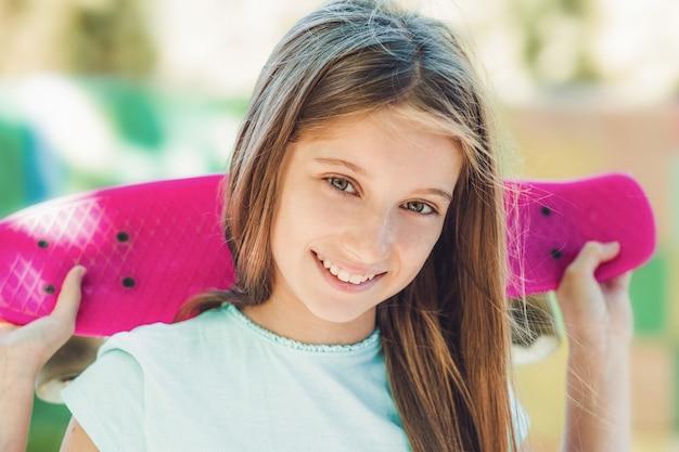 여름에 등 뒤에 분홍색 스케이트보드를 들고 웃고 있는 10대 소녀의 근접 촬영 초상화