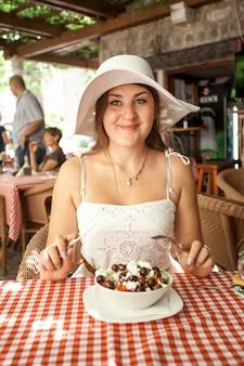 레스토랑에서 샐러드를 먹고 웃는 여자의 근접 촬영 초상화