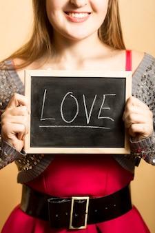 Портрет крупным планом улыбающейся женщины, держащей доску со словом «любовь»