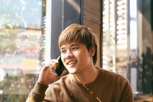 Портрет крупным планом улыбающегося молодого азиатского человека, говорящего по мобильному телефону и сидящего за пустым столом с размытым интерьером кафе в фоновом режиме