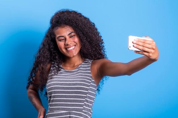 셀카 사진을 복용 스마트 폰을 들고 웃는 젊은 매력적인 아프리카 브라질 여자의 근접 촬영 초상화
