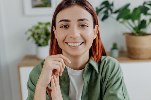 Крупным планом портрет улыбается молодая рыжая женщина дома концепция образа жизни позитивное настроение