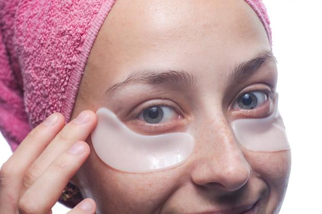 笑顔の若い女性の目の下の白いパッチと青に分離された彼女の頭の上のピンクのタオルのポートレート、クローズアップ。スキンケア